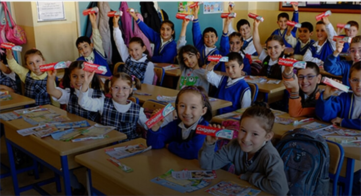 children smiling and holding a Colgate toothpaste box in a classroom