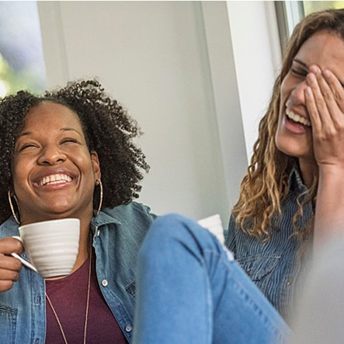 Two women laughing while one of them is holding a coffee mug