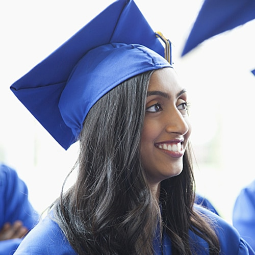 Group of graduates wearing blue cap and gowns smiling