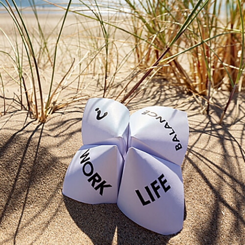 A paper fortune teller laying in the sand with the words work, life, balance, and a question mark on it