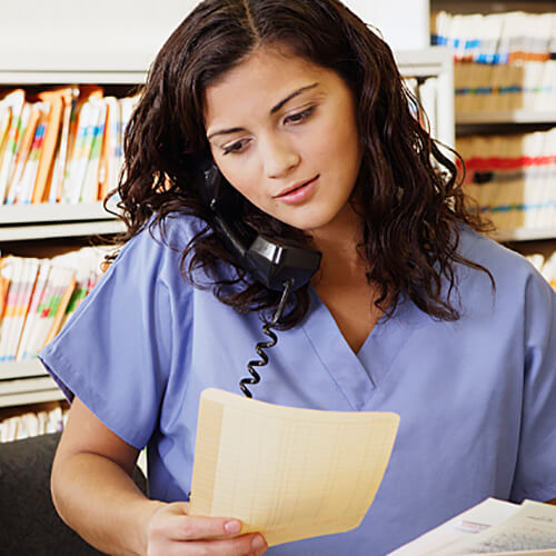 Nurse talking on the phone while holding a piece of paper