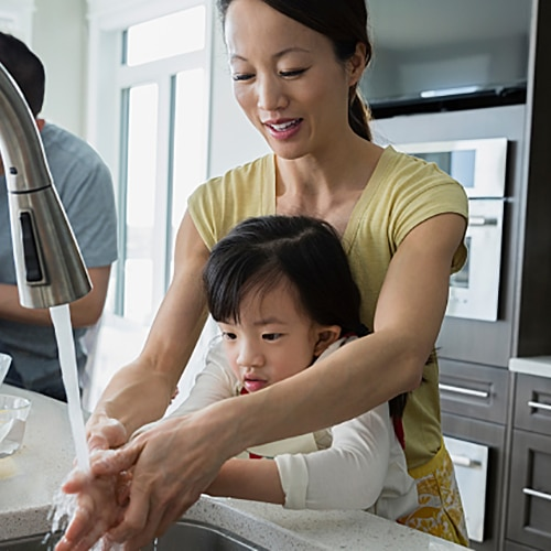 Mother and daughter washing hands while enjoying time with the whole family in the kitchen