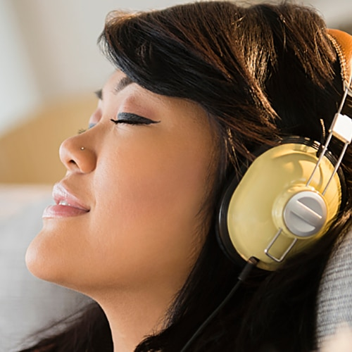Teen resting her head on a pillow with headphones on