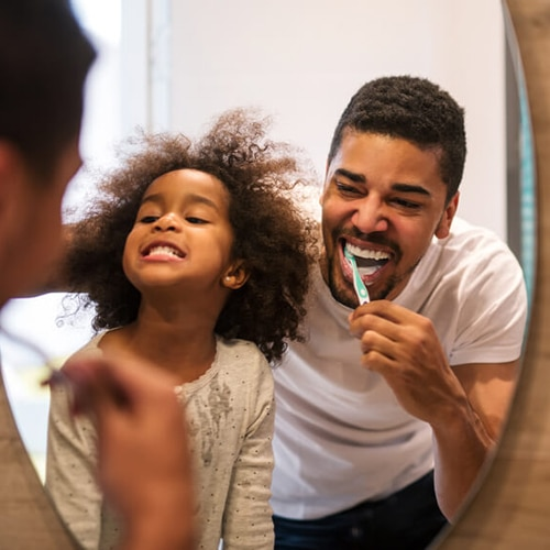 Father and daughter looking at mirror while brushing teeth
