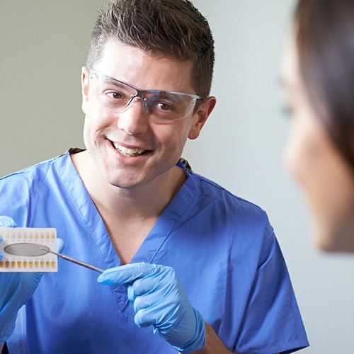 Dentist wearing glasses and gloves showing patient a teeth chart