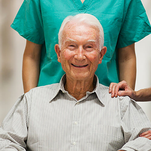Two nurses standing over elderly patient while he smiles