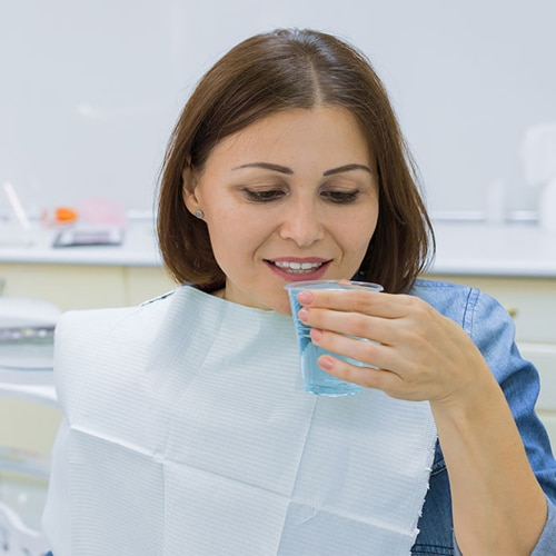 Female patient about to take a sip of mouthrinse