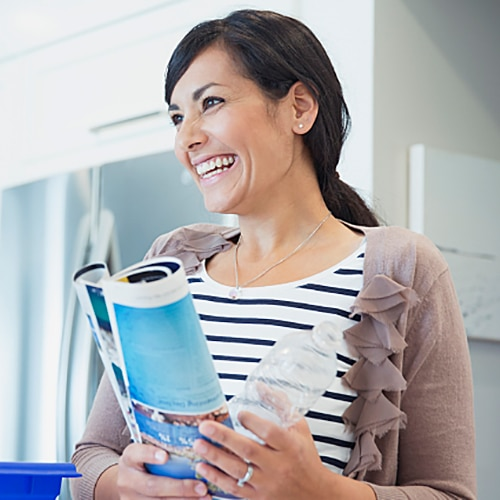 Women in kitchen smiling while holding a pamphlet