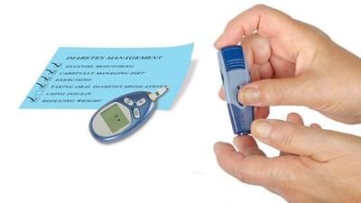Close up of a blood glucose meter and hands using the tool