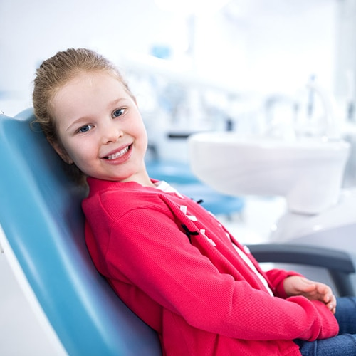 smiling-young girl sitting in dental chair