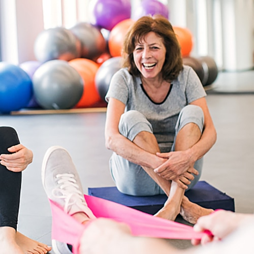 Two women in work-out clothing sitting down on the floor laughing