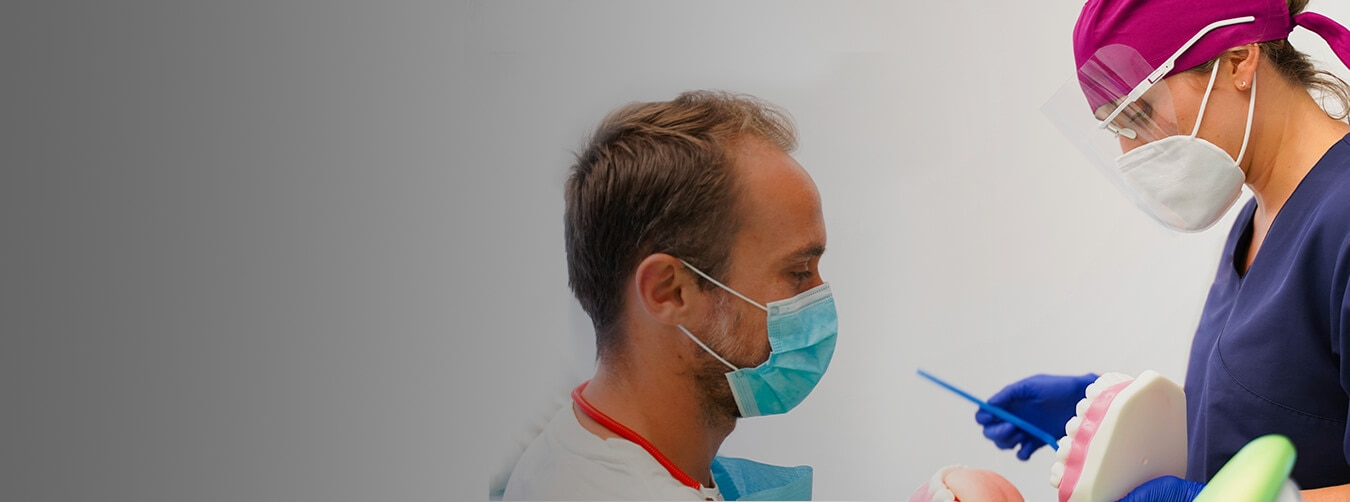 A male patient looking at the hygienist using a short stick to point at a mouth model
